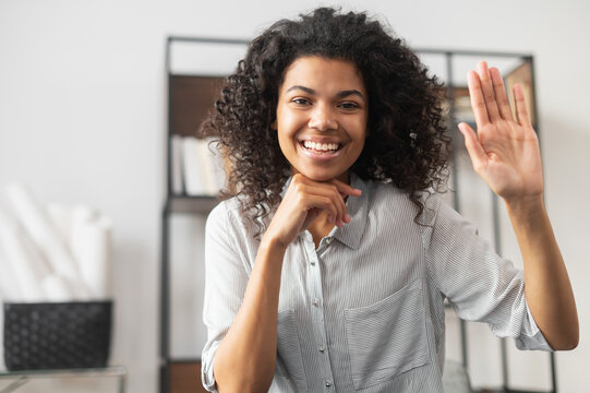 Friendly adorable African American female office worker businesswoman freelancer with Afro hairstyle joyfully waving, smiling and saying hi, making hello sign, greeting and welcoming a newcomer