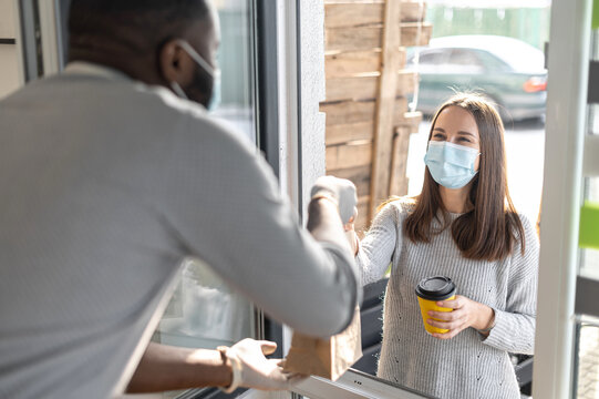 A male cafe worker gives a package with order and cup of takeaway coffee through a window to female customer wearing mask, small business works in conditions coronavirus pandemic