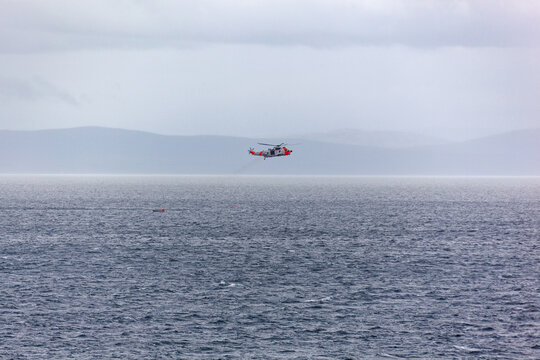 The rescue helicopter saves the fishermen who fell from the boat to the stormy Barents sea, Northern Norway.