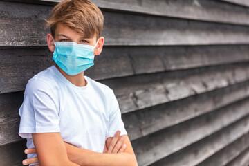 Fototapeta Boy teenager teen male child wearing face mask outside in the Coronavirus COVID-19 pandemic
