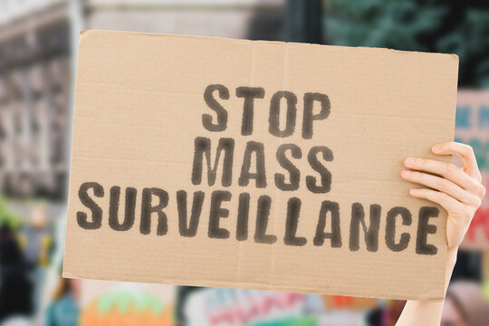"""The phrase """" Stop mass surveillance """" on a banner in hand with blurred background. Control. Spying. Government. Power. Spying. Technology. CCTV. Electronic. Biotechnology. Regulation. Illegal"""
