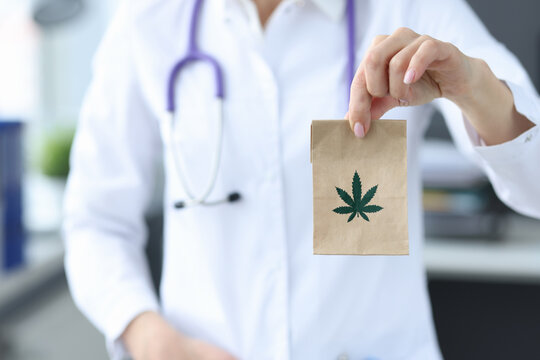 Doctor holding package with marijuana in clinic closeup