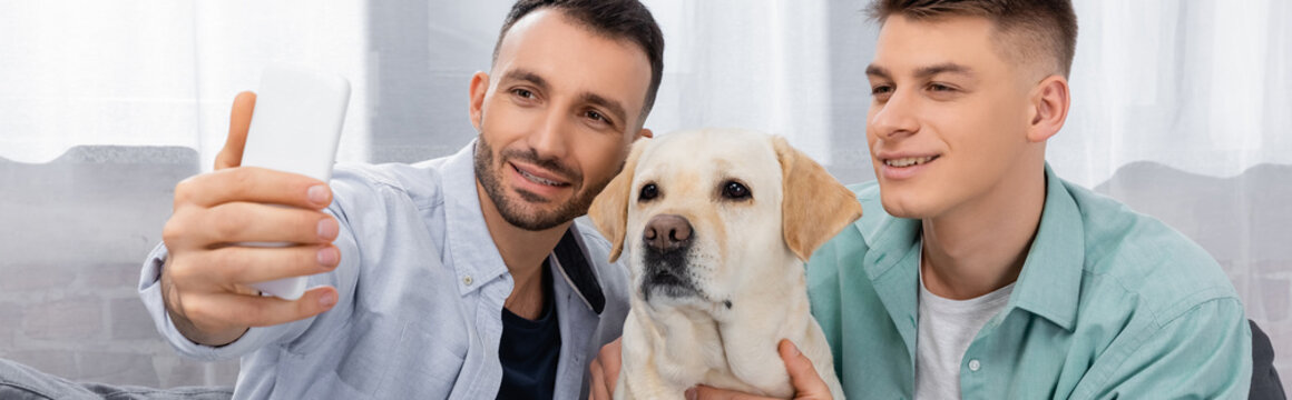 cheerful same sex couple smiling and taking selfie with labrador, banner