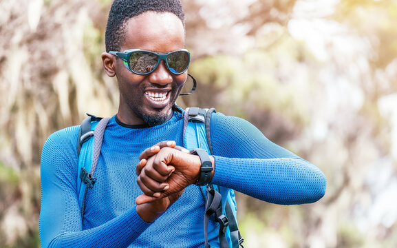 Portrait of a cheerfully smiling African-American Ethnicity young man checking a heartrate or distance on wrist smartwatch in the forest during a hiking walk. Active people and sport lifestyle concept