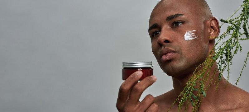Mixed-race man raising a skin care cream near plant