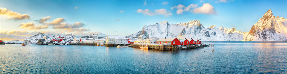 Traditional Norwegian red wooden houses (rorbuer) on the shore of  Reinefjorden near Hamnoy village.