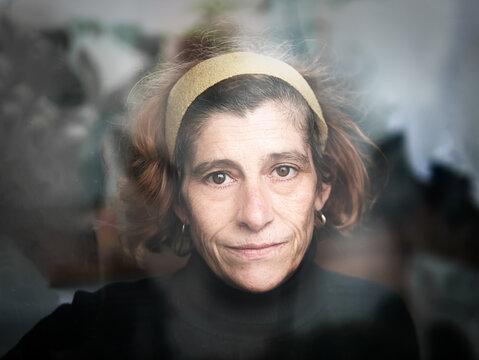 Mature woman natural light portrait behind a window