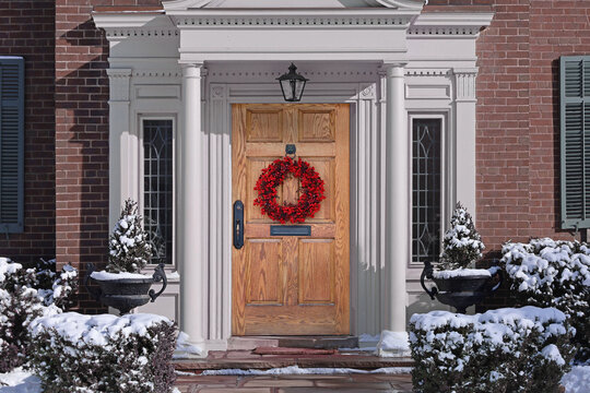 Wood grain front door of house with colorful Christmas wreath and snow covered evergreen bushes