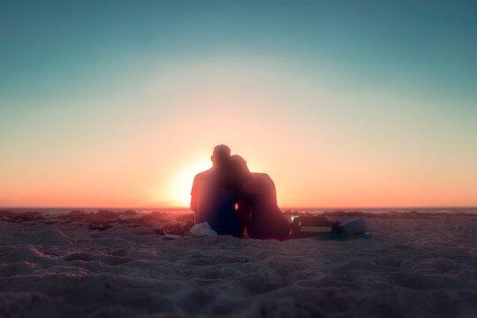 Pareja de enamorados sentados en la playa mirando el amanecer