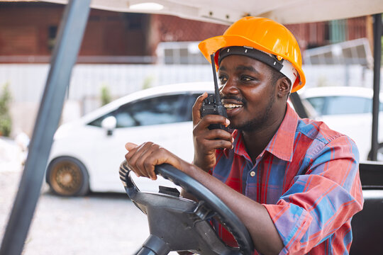 Afro loader worker is talking on the walkie-talkie in forklift.