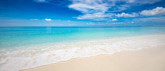 Fototapeta Closeup of sand on beach and blue summer sky. Panoramic beach landscape. Empty tropical beach and seascape. Blue sky, soft sand, calmness, tranquil relaxing sunlight, summer mood. Travel vacation