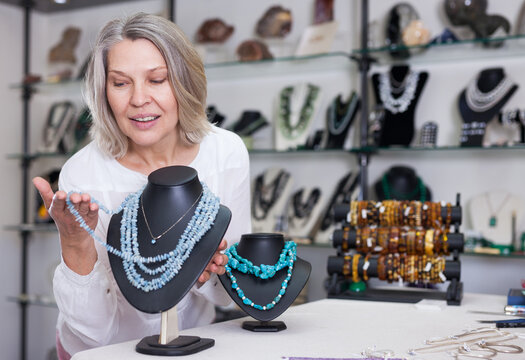 Woman trying on a turquoise necklace and earrings at a jewelry store. High quality photo
