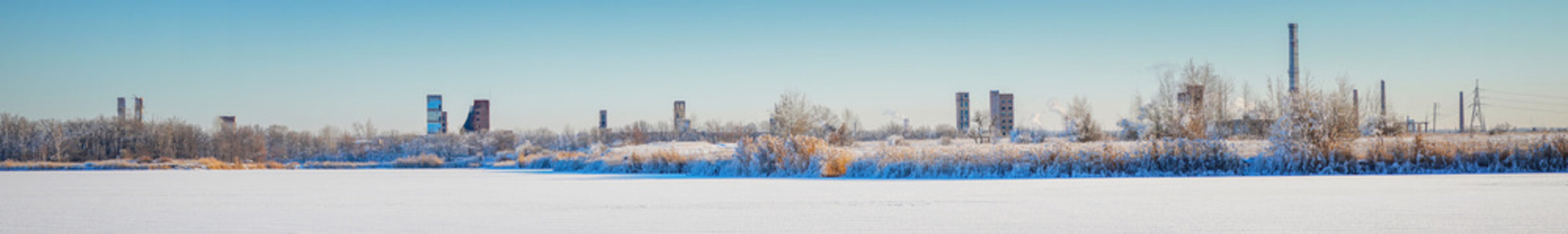 An abandoned old chemical plant on the bank of a frozen winter river covered with snow