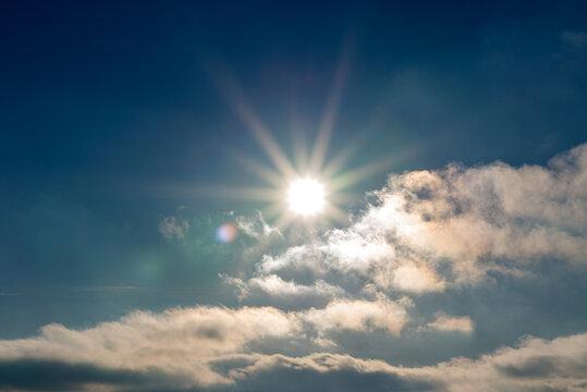 Sunset blue sky, bright sun shines through clouds.