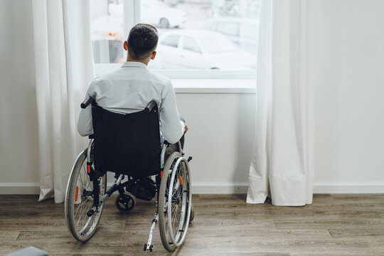 Young disabled man sitting in a wheelchair near the window