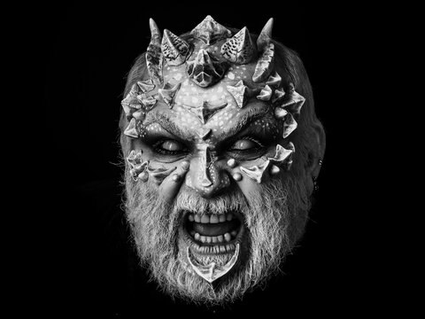 Evil face with dragon skin and grey beard. Demon baring teeth isolated on black. Horror and fantasy concept. Monster with thorns and horns.