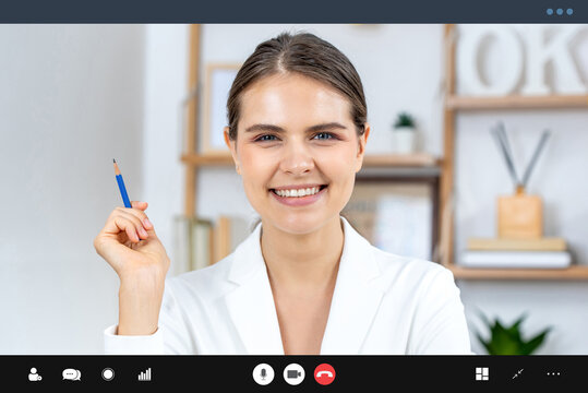 Smiling Caucasian woman in formal business suit looking at camera while making video call, work from home and online interview concepts