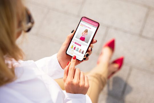 Woman shopping for new dress online on her mobile phone