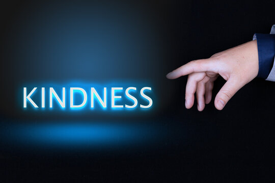 KINDNESS text, word written in neon letters on a black background pointed to by a hand with a person's index finger.