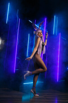 A slender sexy girl dancer in a sensual rabbit costume stands in full growth against a background of blue lights and smoke.