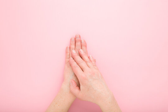 Mature woman hands on light pink table background. Pastel color. Closeup. Point of view shot. Care about clean, beautiful, soft hands skin and nails in old ages. Top down view.
