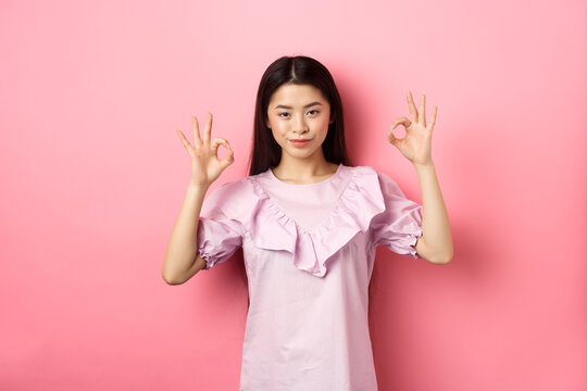 Smiling asian woman showing okay signs and looking confident, assure all good, praise good work, nice choice gesture, standing on pink background