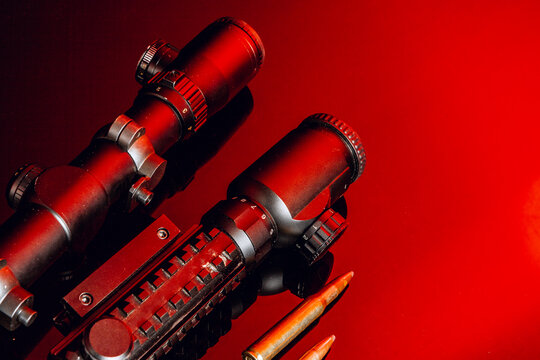 Optical scope for rifle on black background with red light