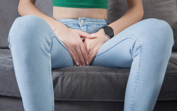 Young woman sitting on sofa suffering a bladder pain.