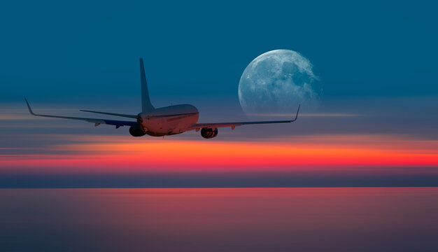 """Passenger airplane flying away in to sky high altitude during sunset with full moon """"Elements of this image furnished by NASA"""""""