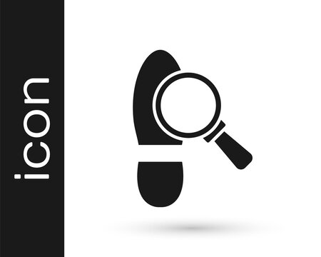 Black Magnifying glass with footsteps icon isolated on white background. Detective is investigating. To follow in the footsteps. Vector.