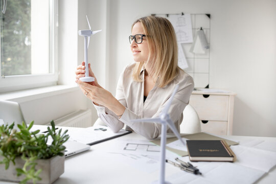 pretty blonde business woman is sitting in her office working on new alternative energy development looking at a model of a wind turbine and is happy and motivated