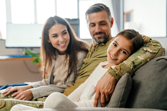 Happy masculine military man hugging his family while sitting on sofa