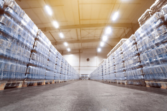 Huge industrial warehouse with stacks of vacuum-packed water or beer packages on pallets. Front view. Selective focus
