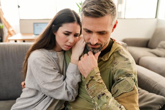 Sad young military soldier saying goodbye to sad wife