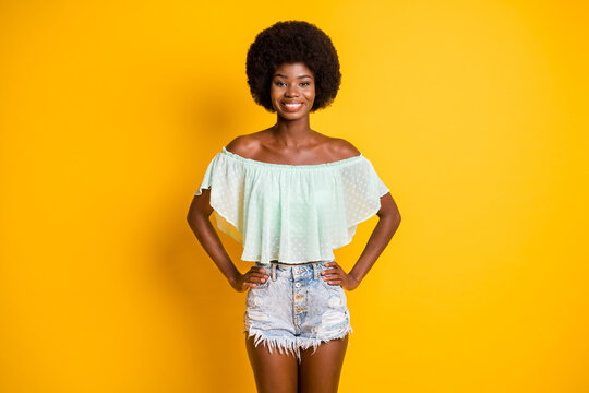 Photo portrait of girl with two hands on waist isolated on vivid yellow colored background