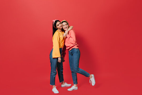 Full-length shot of girls in jeans and sweatshirts hugging on red background