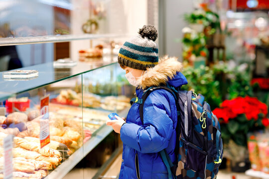 Kid boy wearing medical mask buy bread and pastry for school lunch in bakery. Child with backpack and winter clothes. Schoolkid during lockdown and quarantine time during corona pandemic disease