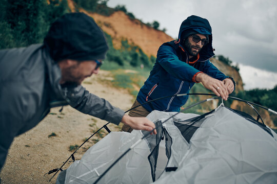Two hikers adjusting tent on camping trip while standing in a nature.
