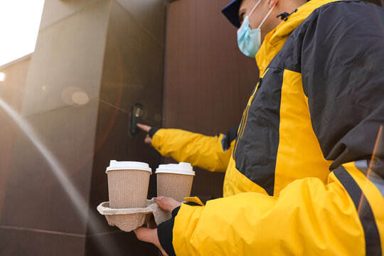 Courier in medical mask holding takeaway drinks and ringing doorbell outdoors, focus on paper cups. Delivery service during quarantine due to Covid-19 outbreak