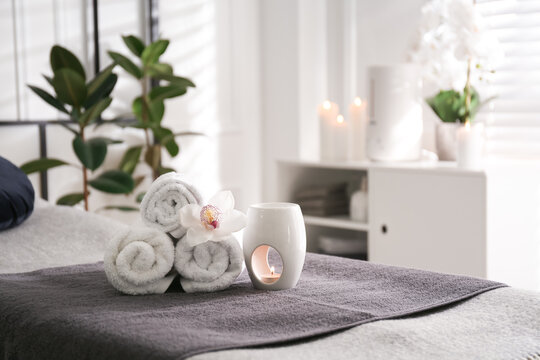 Towels, aroma lamp and orchid flower on couch in spa salon