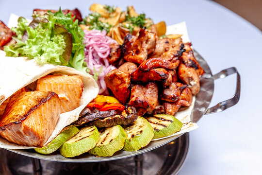 Mixed grill meat fried vegetables and grilled salmon fish fillets decoration in warm dish. Assorted delicious grilled kebab served with herbs on platter. Restaurant menu barbecue plate Bbq party meal