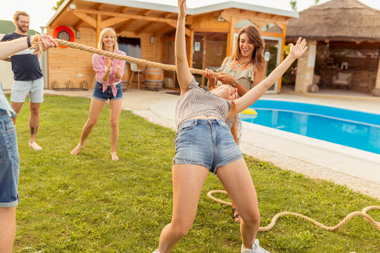 Friends having fun doing limbo dance at summer party by the pool