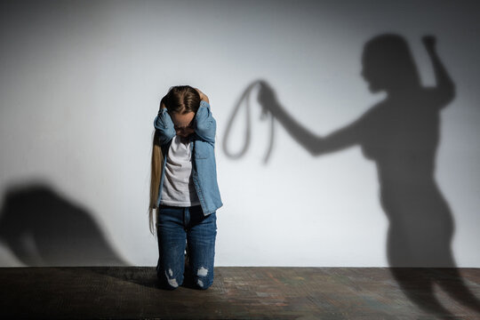Domestic violence, abusing. Scared little caucasian girl, victim sitting close to white wall with shadow of angry mother's threatening on it. Awareness of social problem, childhood, physical violence.