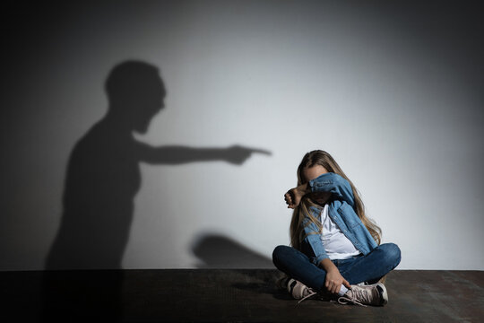 Domestic violence, abusing. Scared little caucasian girl, victim sitting close to white wall with shadow of angry father's threatening on it. Awareness of social problem, childhood, physical violence.