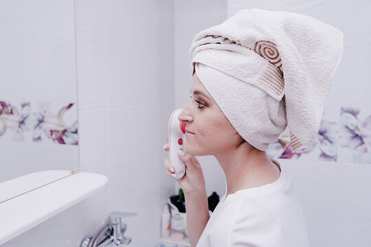 Portrait of a young woman with bad skin removing makeup with cleansing brush, device for household Washing and massage Face, applying spa procedures, Female facial skin care, clean the pores of dirt