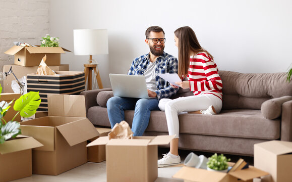 Cheerful couple with laptop discussing insurance of new home