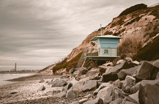Lifeguard tower on an empty beach full of big rocks under the cloudy sky