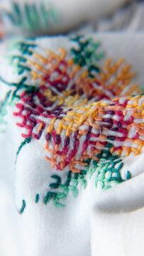 Bordado de flores con hilos de colores en mantel de hilo blanco