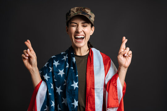 Delighted soldier woman with american flag holding fingers crossed