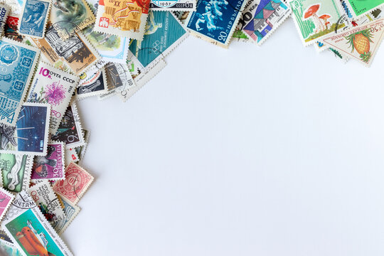 Corner frame border made of multicolored postage stamps collection from different countries on white background